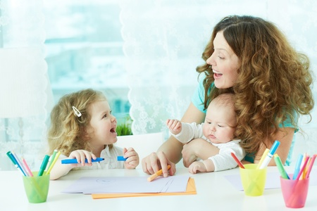 babysitter: Beautiful mother and her children drawing at home