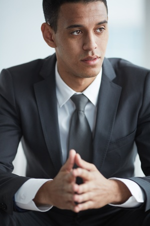 A young serious businessman in suit concentrating on something photo