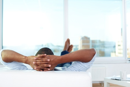 head rest: Image of young African man lying on sofa and having rest Stock Photo