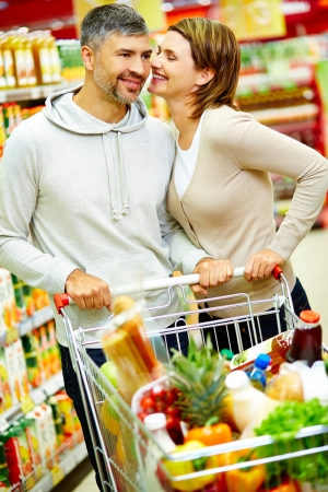 Image of happy couple with cart flirting in supermarket photo