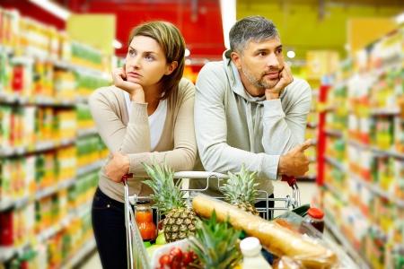 mujeres tristes: Imagen de la joven pareja con carrito de supermercado