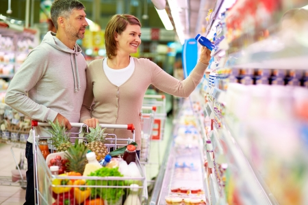 shoppers: Image of happy couple with cart choosing products in supermarket Stock Photo