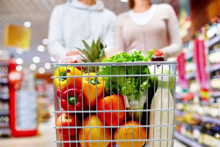 supermarket cart: Image of cart full of products in supermarket being pushed by couple