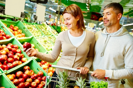 Image of happy couple choosing apples in supermarket photo