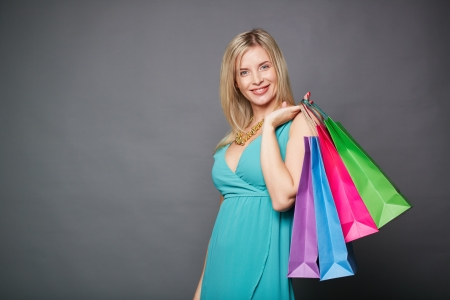 shopaholism: Portrait of happy female satisfied with her lucky shopping over grey background
