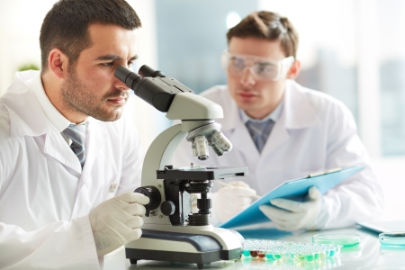 research study: Serious clinicians studying chemical elements in laboratory