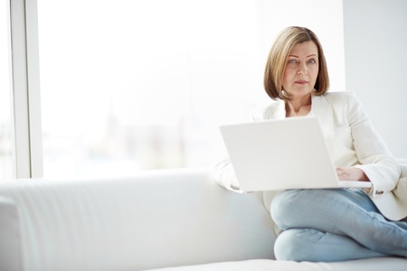 Portrait of mature woman with laptop sitting on sofa and looking at camera photo