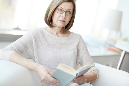 mid age: Portrait of mature woman with book looking at camera