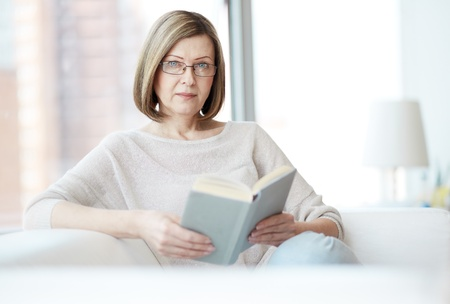 woman wearing glasses: Portrait of mature woman with book looking at camera