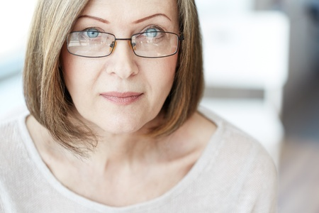 serious: Mature woman in eyeglasses looking at camera