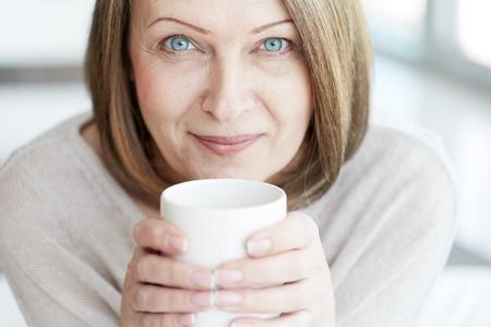 yeux: Portrait de femme m�re avec une tasse en regardant la cam�ra
