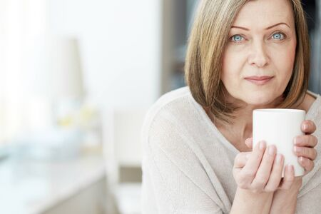 Portrait of mature woman with cup looking at camera Stock Photo