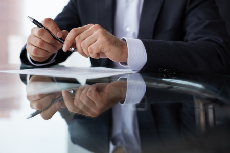sign contract: Close-up of male hands with pen over document