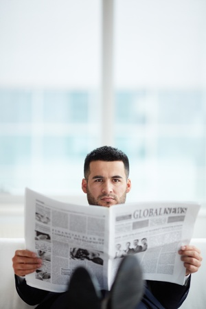 newspaper reading: A young businessman with newspaper looking at camera Stock Photo