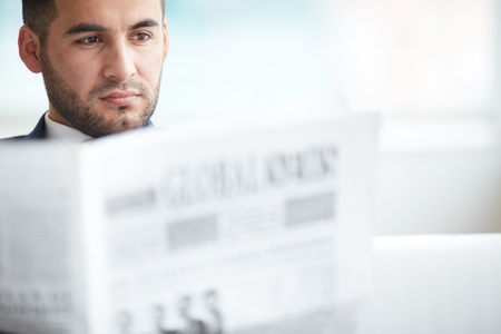 A young serious businessman reading newspaper photo