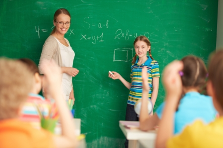 youthful: Portrait of smart teacher and schoolgirl standing by blackboard and looking at schoolkids in classroom Stock Photo