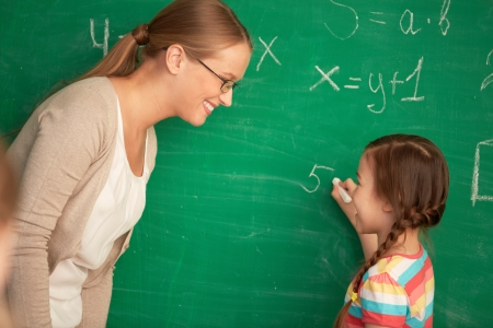 Portrait of smart teacher and schoolgirl standing by blackboard and looking at one another photo