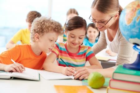 diligente: Retrato de diligente dibujo colegiala en la lecci�n rodeada de su compa�ero y maestro