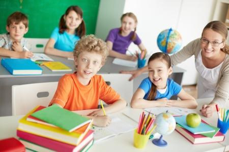 diligente: Retrato de colegiales diligentes y maestro mirando a la c?ra en la lecci?