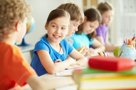 niÑos hablando: Retrato de alumno aplicado feliz mirando a su compañero de clase en la lección