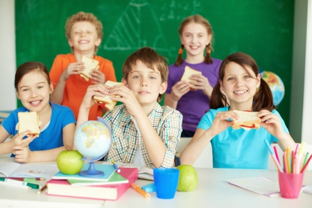 Portrait of cute schoolchildren with sandwiches looking at camera in classroom  photo