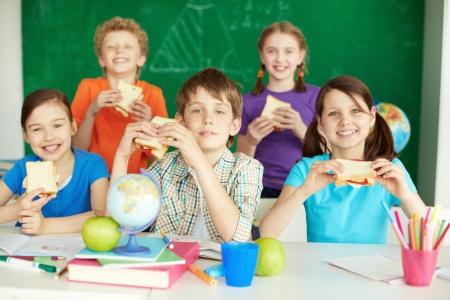 botanas: Retrato de los escolares lindo con bocadillos mirando a la c�mara en el aula Foto de archivo