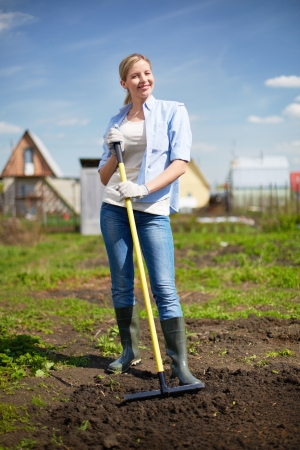 vertical garden: Image of happy female farmer looking at camera while working in the garden