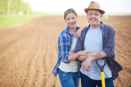 plowed: Image of two happy farmers on background of plowed field