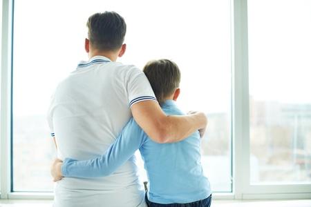 그의 아들을 껴 안은 남자의 후면보기