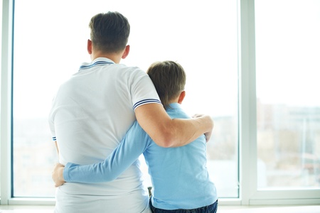 kid's day: Rear view of man embracing his son