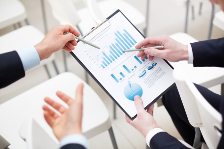 analyzed: Close-up of graph and chart analyzed by businessmen