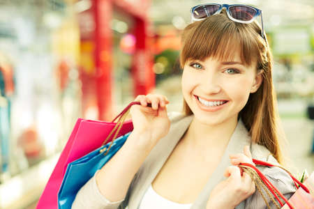 shopaholism: Pretty young shopper with shopping bags smiling at camera