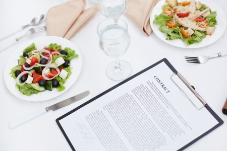 paper plates: Close-up of business contract and lunch on the table Stock Photo