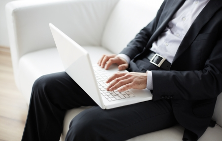 Close-up of businessman sitting on sofa and typing on laptop photo