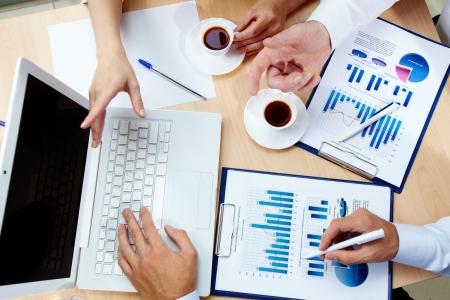empleado de oficina: Este punto de vista del negocio de personas discutiendo los datos financieros