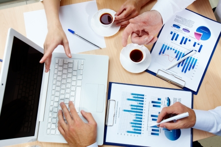 office worker: The above view of business people discussing financial data