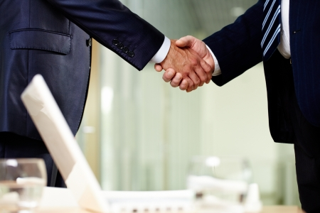 Close-up of two men handshaking after making agreement