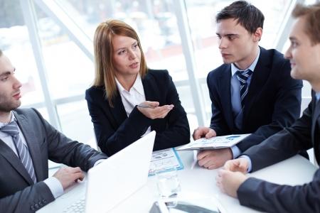 personas escuchando: Elegantes socios de negocios escucha a alg?n conocido a satisfacer Foto de archivo