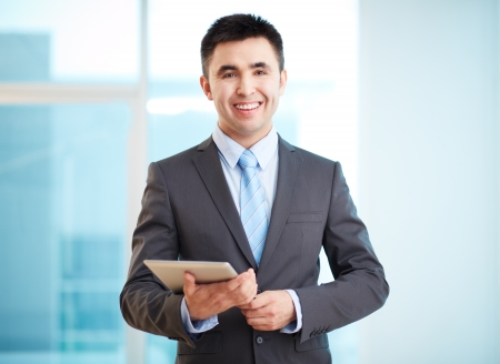 Portrait of cheerful businessman with touchpad looking at camera photo
