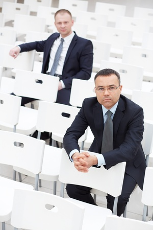 serious businessman: Confident businessmen sitting on chairs of conference hall