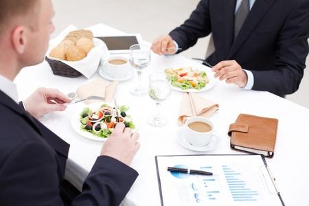 Close-up van zakenlieden zitten in een cafe en het hebben van zakelijke lunch Stockfoto
