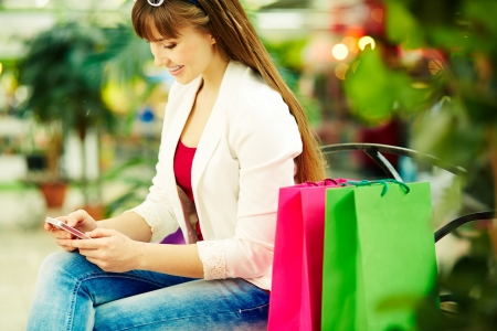 shopaholism: Pretty lady with colorful shopping bags sitting in trade center and writing sms