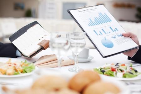 negocios comida: Close-up de Bloc de notas abierto y documento de negocio en manos de los hombres durante el almuerzo de negocios