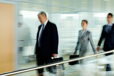 go inside: Tired businessman going along corridor with two employees behind Stock Photo