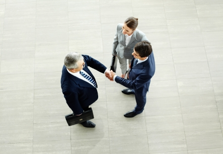 ovation: Image of business partners handshaking after striking deal with smart woman near by Stock Photo