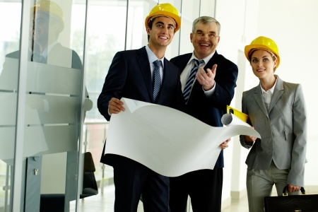 сooking: Three architects standing in office building and ooking at camera while planning work Stock Photo