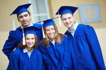 the alumnus: Friendly students in graduation gowns looking at camera