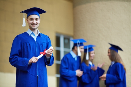 alumnus: Friendly students in graduation gowns interacting with confident guy in front Stock Photo