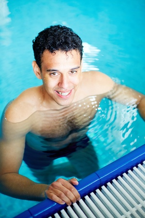 Image of young male looking at camera in swimming pool photo