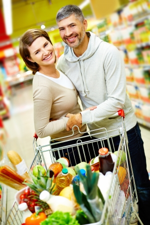 Image of happy couple with cart full of products looking at camera in supermarket photo